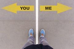Dig eller mig textpilar på asfaltjordning, fot och skor på golv Arkivfoton