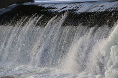 Diga, cascata la corrente del fiume cade dalla diga nell'inverno diga ghiacciata con una forte corrente del fiume gocce brillanti fotografia stock