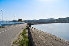 Diga di idropotenza sul fiume di Olt in un giorno di molla soleggiato Pianta idroelettrica sul lago artificiale fotografia stock