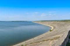 Diga di idropotenza sul fiume di Olt in un giorno di molla soleggiato Pianta idroelettrica sul lago artificiale fotografia stock libera da diritti