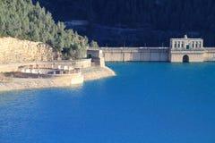 Diga e scolo con acqua luminosa blu Fotografia Stock