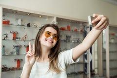 Diga o queijo à câmera Retrato da mulher atrativa na compra na loja do ótico que toma o selfie e que mostra o sinal de v quando imagens de stock royalty free