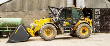 Digger φορτωτής κατασκευής στο αγροτικό ναυπηγείο με τη σιταποθήκη Στοκ Φωτογραφία