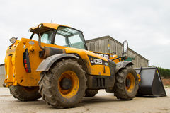 Digger φορτωτής κατασκευής στο αγροτικό ναυπηγείο με τη σιταποθήκη Στοκ εικόνες με δικαίωμα ελεύθερης χρήσης