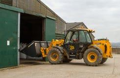 Digger φορτωτής κατασκευής στο αγροτικό ναυπηγείο με τη σιταποθήκη Στοκ Εικόνες