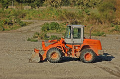 Digger. A digger awaiting arrival of truck to load with gravel from river beach Royalty Free Stock Photo