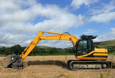 Digger. Yellow digger standing idle on a building construction site with rural countryside and a blue sky with clouds to the rear Royalty Free Stock Photos