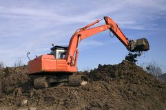 Digger #2. Construction digger on a mound of earth, bucket tipping royalty free stock photos