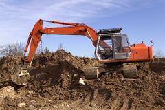 Digger. Construction digger on a mound of earth stock photos