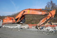 Digger. Huge orange digger with a long arm in a site stock image