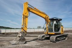 Digger. Industrial yellow digger standing idle on a building site with a blue sky to the rear royalty free stock photos
