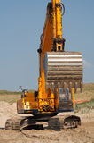 Digger 7363. Orange earth moving machine in the sand with blue background sky royalty free stock photo