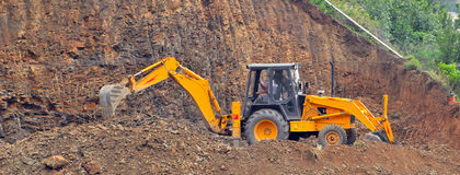 Digger. Working on mountain side royalty free stock photography