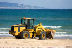 Digger. Articulated Digger clears sand on beach in Spain. Mountains in background. Sea and sand royalty free stock photo