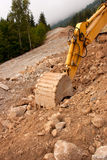 Digger in action. A yellow digger or excavator used to prepare a new track in the mountains Royalty Free Stock Photos