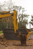 Digger arm with dumpster behind. Yellow digger arm with dumpster skip  behind on worksite Stock Image