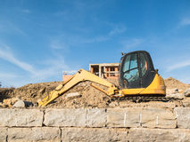 Digger on a construction site building a stone wall Royalty Free Stock Images