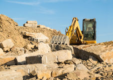 Digger on a construction site building a stone wall Stock Photo