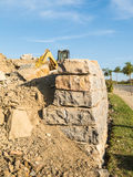 Digger on a construction site building a stone wall Stock Photography