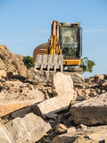 Digger on a construction site building a stone wall Royalty Free Stock Photography