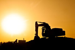 Digger on construction site with giant sun. Silhouette of a Digger on a construction site with working man, giant sun before orange sky in background royalty free stock photography
