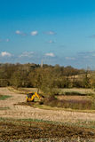 Digger in countryside clearing ditch Stock Image
