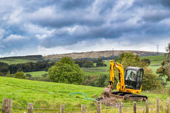 Digger in the Countryside. A digger preparing a trench for a water main in the English Countryside royalty free stock photography