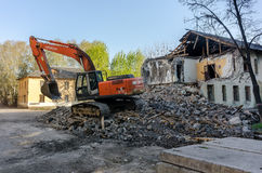 Digger demolishing houses for reconstruction Stock Photos
