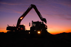 Digger and Dumper. Silhouette of a mechanical digger loading an articulated dump truck or dumper early in the morning at sunrise stock photo