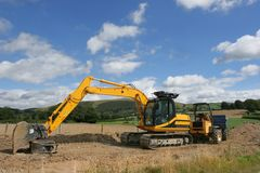 Digger and Dumper Truck. Earthmover and dumper truck standing idle on a new building construction site with rural countryside and a blue sky with clouds to the Royalty Free Stock Image