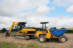 Digger and Dumper Truck. Standing idle on a building site in rural countryside Royalty Free Stock Images