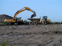 Digger and dumper truck working on waste ground reclamation Stock Photos
