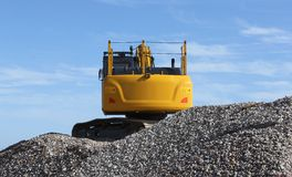 Digger excavator on the beach. The back of a yellow excavator moving shingle from the beach Stock Photo