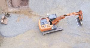 Digger excavator construction building site banner view from above miniature rubber tracks orange vehicle in operation excavating. Digger excavator construction royalty free stock photos