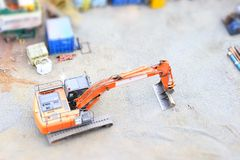 Digger excavator construction building site banner view from above miniature rubber tracks orange vehicle in operation excavating. Digger excavator construction stock photo