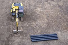 Digger excavator construction building site banner view from above miniature rubber tracks yellow vehicle in operation excavating. Digger excavator construction royalty free stock images