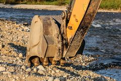 Digger excavator machine bucket digging stones ground by the river royalty free stock photo