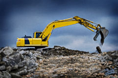 Digger excavator with raised boom. Excavator loader at construction site with raised bucket with blue sky background Stock Images