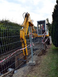 Digger, fence, street. Digging small street sewage system in the middle of road with yellow excavator. Construction site area stock images