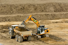 Digger filling truck with soil Stock Photo