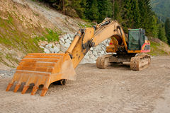 Digger front view. A yellow digger or excavator used to prepare a new track in the mountains Stock Images
