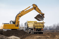 Digger loading trucks with soil Stock Image
