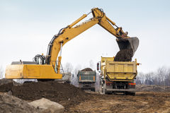 Digger loading trucks with soil Royalty Free Stock Image