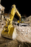 Digger with mechanical arm on the ruins of a house at night. In wide angle shot Royalty Free Stock Photography