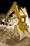 Digger with mechanical arm on the ruins of a house at night. In wide angle shot Stock Photos