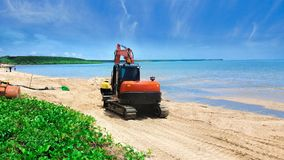 Digger moving beach sand after erosion. Excavator or digger moving beach sand after erosion on a tropical beach with calm ocean in Cairns, Queensland, Australia Stock Photos