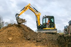 A digger moving soil. A digger excavator dumping soil while laying footings stock images