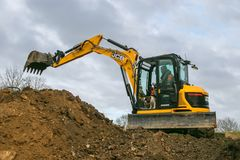 A digger moving soil. A digger excavator dumping soil while laying footings royalty free stock photography