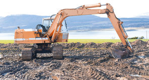 Digger in operation at the coast. Royalty Free Stock Photography