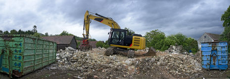 Digger with a picker arm on a mountain of rubble. A digger with a picker arm on a mountain of rubble from the demolition of a residential house and two skips Stock Photography